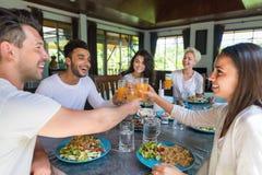Groupe des jeunes prenant le petit déjeuner ensemble, boisson intérieure de nourriture de matin de cuisine d'amis Photo stock