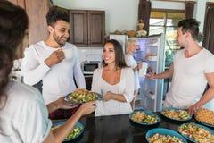 Groupe des jeunes prenant le petit déjeuner ensemble, boisson intérieure de nourriture de matin de cuisine d'amis Photographie stock libre de droits