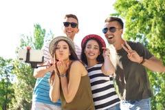 Groupe des jeunes prenant le selfie avec le monopod dehors Images libres de droits