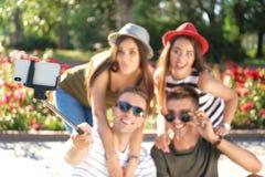 Groupe des jeunes prenant le selfie avec le monopod dehors, foyer sur le smartphone Image stock