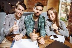 Groupe des jeunes réussis heureux montrant le pouce  Photographie stock libre de droits