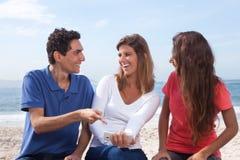 Groupe des jeunes regardant des photos sur le smartphone Photos stock