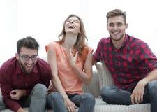 Groupe des jeunes riant et s'asseyant sur le divan Image libre de droits