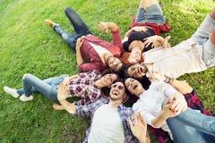 Groupe des jeunes s'étendant sur l'herbe en cercle, heureux Image stock
