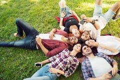 Groupe des jeunes s'étendant sur l'herbe, souriant Images stock