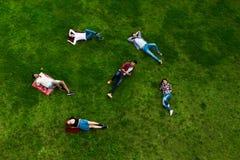 Groupe des jeunes s'étendant sur l'herbe, souriant Photo stock