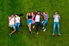 Groupe des jeunes s'étendant sur l'herbe, souriant Photographie stock