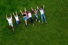 Groupe des jeunes s'étendant sur l'herbe, souriant Photographie stock libre de droits