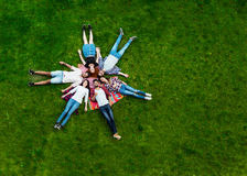 Groupe des jeunes s'étendant sur l'herbe, souriant Photo libre de droits