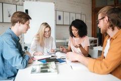 Groupe des jeunes s'asseyant à la table et travaillant ensemble dans le bureau Deux jolies filles et deux garçons pensivement Photos libres de droits