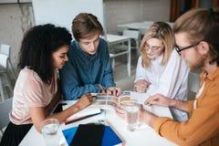 Groupe des jeunes s'asseyant à la table et travaillant ensemble Deux jolies filles et deux garçons discutant quelque chose Images libres de droits