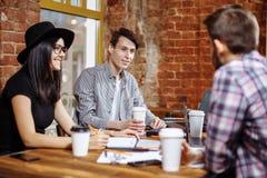 Groupe des jeunes s'asseyant à un café, café potable et discutant de nouvelles idées Photo stock