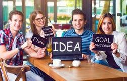 Groupe des jeunes s'asseyant à un café, tenant les instruments électroniques Photos stock