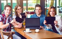 Groupe des jeunes s'asseyant à un café, tenant les instruments électroniques Photographie stock libre de droits