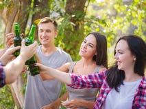 Groupe des jeunes s'asseyant autour d'une table dehors Ils apprécient pour causer et boire des bières Photos stock