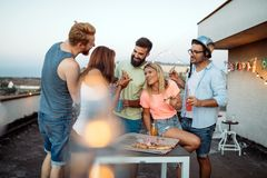 Groupe des jeunes s'asseyant autour et mangeant de la pizza Image libre de droits