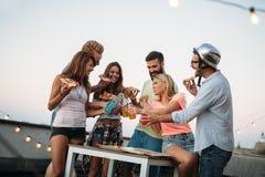 Groupe des jeunes s'asseyant autour et mangeant de la pizza Photo stock