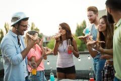 Groupe des jeunes s'asseyant autour et mangeant de la pizza Photo libre de droits