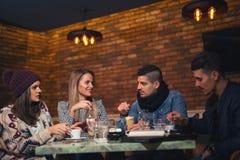 Groupe des jeunes s'asseyant dans un café Images stock