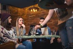 Groupe des jeunes s'asseyant dans un café ayant l'amusement Image libre de droits