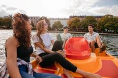 Groupe des jeunes s'asseyant sur le bateau de pédale dans le lac Images stock