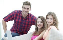 Groupe des jeunes s'asseyant sur le divan dans le salon Photographie stock