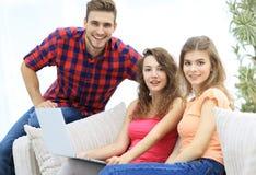 Groupe des jeunes s'asseyant sur le divan dans le salon Images libres de droits