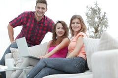 Groupe des jeunes s'asseyant sur le divan dans le salon Photo stock