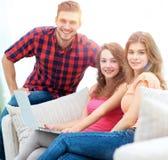 Groupe des jeunes s'asseyant sur le divan dans le salon Image stock