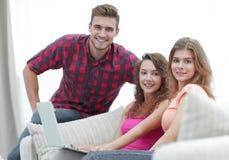 Groupe des jeunes s'asseyant sur le divan dans le salon Photos libres de droits