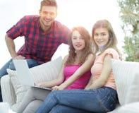 Groupe des jeunes s'asseyant sur le divan dans le salon Images stock
