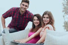 Groupe des jeunes s'asseyant sur le divan dans le salon Image libre de droits