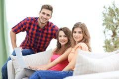 Groupe des jeunes s'asseyant sur le divan dans le salon Photographie stock libre de droits