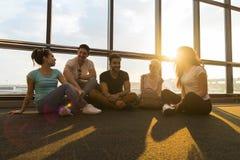Groupe des jeunes s'asseyant sur le plancher dans le départ de attente de Windows de salon d'aéroport parlant les amis heureux de Images stock