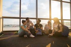 Groupe des jeunes s'asseyant sur le plancher dans le départ de attente de Windows de salon d'aéroport parlant les amis heureux de Photographie stock