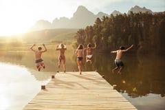 Groupe des jeunes sautant dans l'eau d'une jetée Images stock