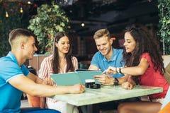 Groupe des jeunes se réunissant dans un café Photo stock