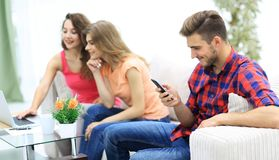 Groupe des jeunes se reposant sur le divan dans le salon Photos stock
