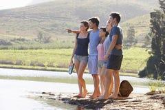 Groupe des jeunes se tenant au rivage du lac éclaboussant l'eau Image libre de droits