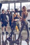 Groupe des jeunes sportifs dans les vêtements de sport s'exerçant au gymnase Photographie stock