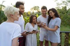 Groupe des jeunes sur l'hôtel tropical de terrasse, amis employant des vacances tropicales de vacances de téléphone intelligent d Photographie stock libre de droits