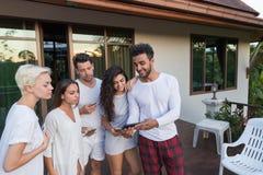 Groupe des jeunes sur l'hôtel tropical de terrasse, amis employant des vacances tropicales de vacances de téléphone intelligent d Photo libre de droits