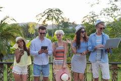 Groupe des jeunes sur l'hôtel tropical de terrasse, amis employant des vacances tropicales de vacances de téléphone intelligent d Images stock