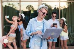 Groupe des jeunes sur l'hôtel tropical de terrasse, amis employant des vacances tropicales de vacances de téléphone intelligent d Photo stock