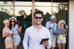 Groupe des jeunes sur l'hôtel tropical de terrasse, amis employant des vacances tropicales de vacances de téléphone intelligent d Photos libres de droits