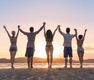 Groupe des jeunes sur la plage aux vacances d'été de coucher du soleil, amis tenant des mains vers le haut de vue arrière de dos  Images libres de droits
