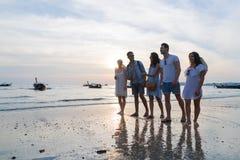 Groupe des jeunes sur la plage aux vacances d'été de coucher du soleil, bord de la mer de marche d'amis Image stock