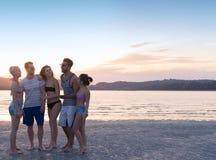 Groupe des jeunes sur la plage aux vacances d'été de coucher du soleil, bord de la mer de marche de sourire heureux d'amis Image stock