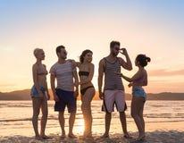 Groupe des jeunes sur la plage aux vacances d'été de coucher du soleil, bord de la mer de marche de sourire heureux d'amis Photos libres de droits
