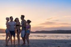 Groupe des jeunes sur la plage aux vacances d'été de coucher du soleil, bord de la mer de marche de sourire heureux d'amis Images libres de droits